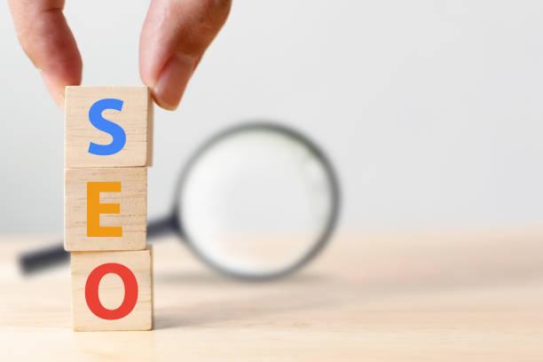 concepto de optimización de motores de búsqueda. mano putting bloque de madera forma de cubo con palabra seo y lupa - seo fotografías e imágenes de stock