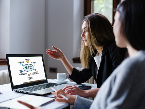 Search Engine Optimization (SEO) Concept On Computer Screen With Two Businesswomen  In The Office