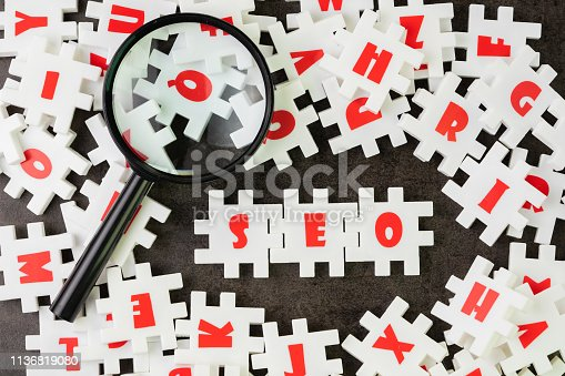 1045434476istockphoto Search Engine Optimization, SEO concept, white puzzle jigsaw with alphabet building the word SEO at the center of dark chalkboard with magnifier glass. 1136819080