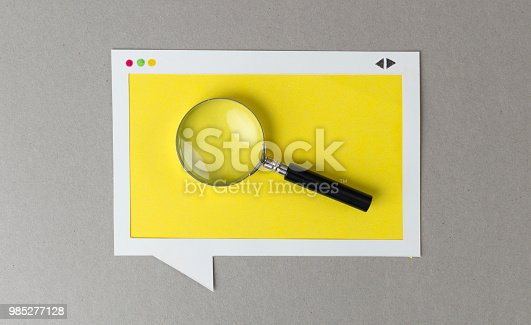 Magnifying glass in the paper browser window frame.
