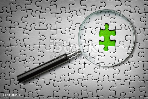 istock Search for missing last puzzle piece with magnifying glass 1179346211
