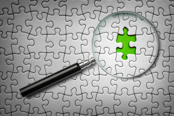 Search for missing last puzzle piece with magnifying glass stock photo