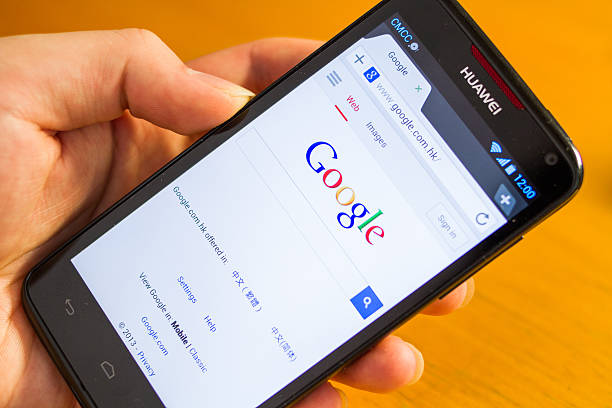 Search with Google Shanghai, China - May 29, 2013: Man searching Google with a Huawei Ascend D1 Qual XL cellphone. Huawei, originated in China, is now a leading global ICT solutions provider. The search engine is powered by Google, an American multinational corporation that provides Internet-related products and services, including internet search, cloud computing, software and advertising technologies. huawei stock pictures, royalty-free photos & images