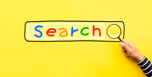 Searching concepts with male hand using magnifying glass with Search text icon on yellow space background stock photo