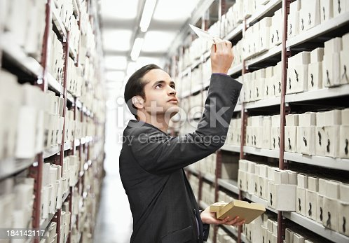 man searching files in a archive with many boxes
