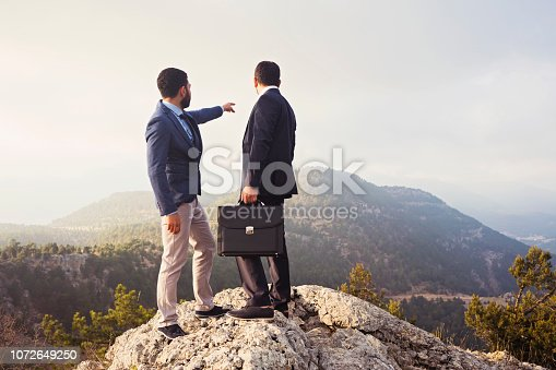 Two businessmen standing on top of mountain.