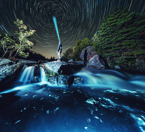 Searching for the Axis A man stands at the top of a river cascade, aiming his headlamp at Polaris, the North Star.  Long exposure. north star stock pictures, royalty-free photos & images