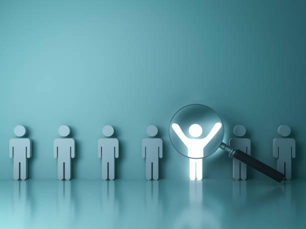 szukając koncepcji właściwej osoby, wyróżnij się z tłumu i innej koncepcji , szkło powiększające koncentrując się na człowieku światła stojącego z szeroko otwartymi ramionami na zielonym tle ściany. renderowanie 3d - indywidualność zdjęcia i obrazy z banku zdjęć