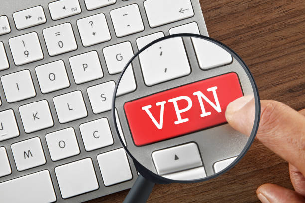 """Searching for VPN key Hand pushing """"VPN"""" key on keypad with magnifying glass vpn stock pictures, royalty-free photos & images"""