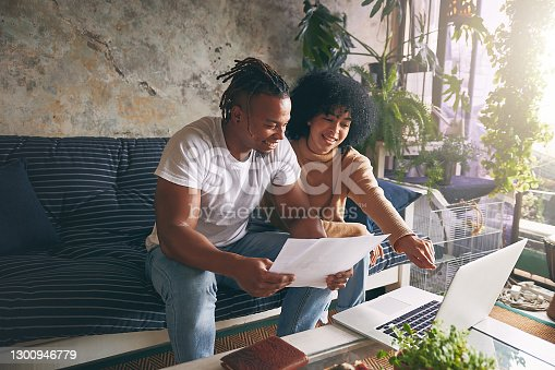 Shot of a young couple using a laptop while going through paperwork together at home