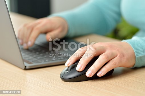 Close up of woman hands working with a laptop and a mouse at home