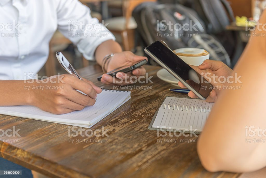 Searching information on smartphone and writing to notes stock photo
