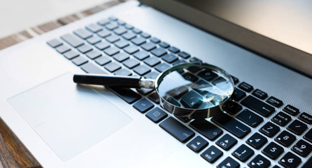 Searching On Internet Concept, Magnifier On Computer Keyboard stock photo