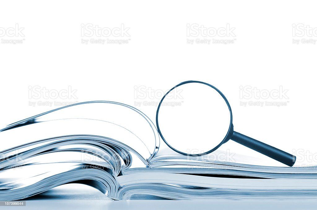 Searching, opened magazines and magnifier glass, side view, isolated white Searching... opened magazines with magnifier glass, side view, isolated on white. Article Stock Photo