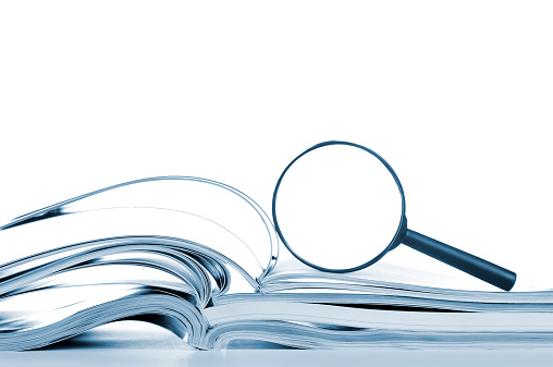 Searching Opened Magazines And Magnifier Glass Side View Isolated White Stock Photo - Download Image Now