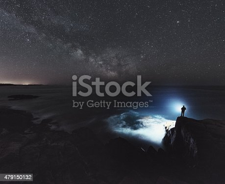 A man is silhouetted against the light of a bright spotlight as he searches the Atlantic under the Summer Milky Way.  Long exposure.