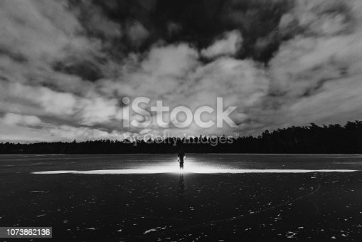 A man stands on a frozen lake with a bright spotlight.  Long exposure.