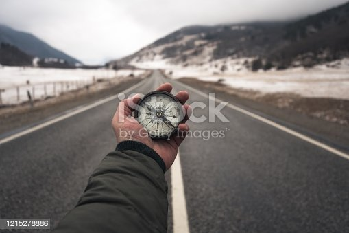 Searching the way. Man stands on a road and holds compass in hand.