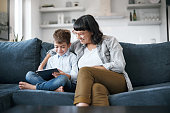 Shot of a mother and her little son using a digital tablet together at home