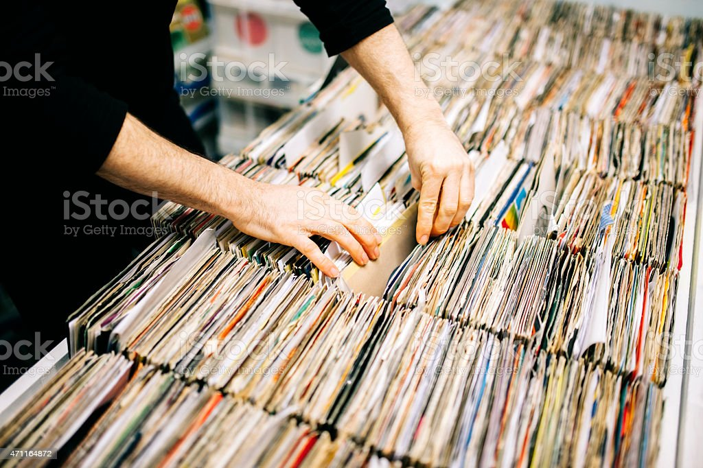 Searching through second hand vinyl records in a record store stock photo
