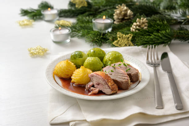 seared duck breast with brussels sprout, duchess potatoes and sauce as a festive dinner, served on a white wooden table with candles fir branches and christmas decoration - duchessa foto e immagini stock