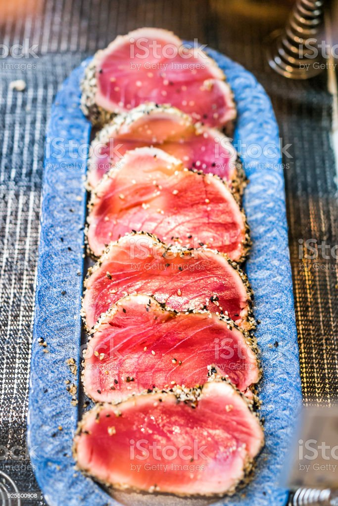 Seared raw ahi tuna rare steaks with black pepper crust on display in market, restaurant, shop, deli counter, sesame seeds stock photo