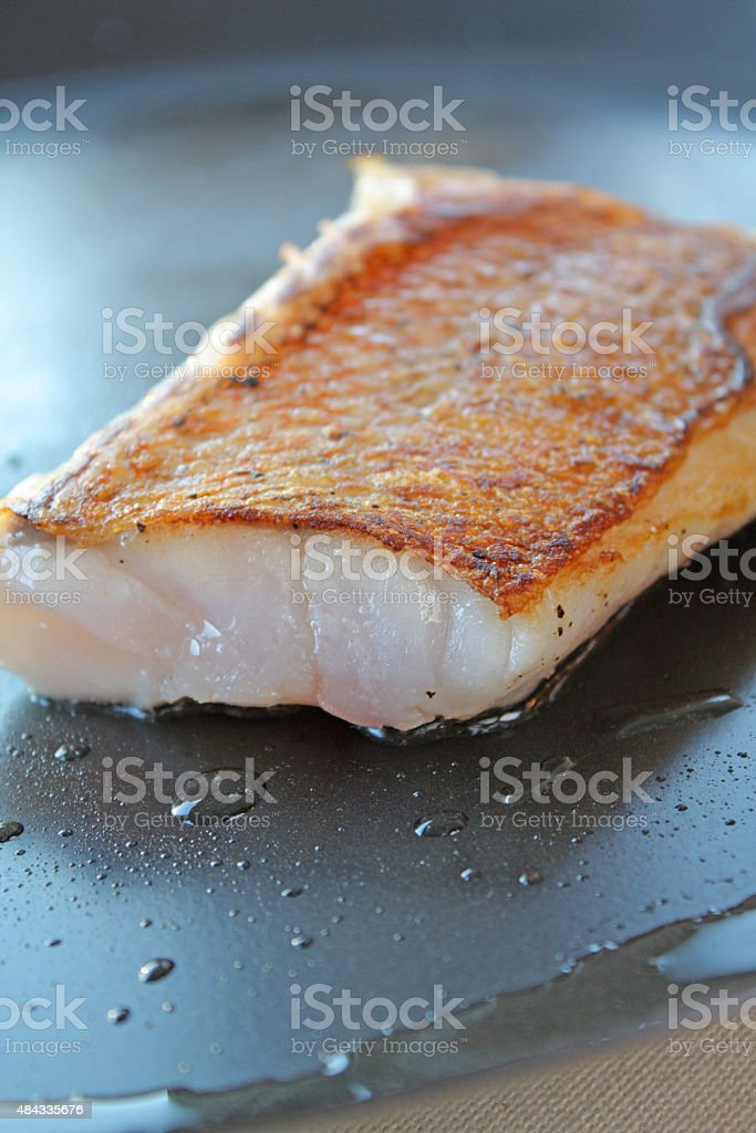 Seared Rockfish Fillet with Skin On in a Hot Pan stock photo