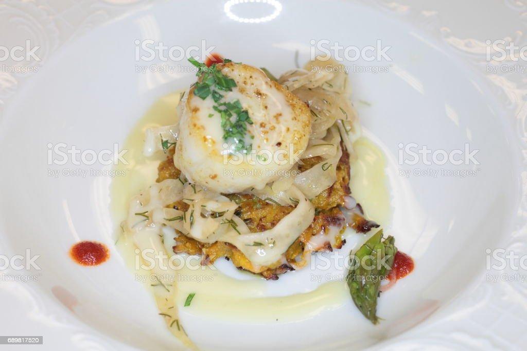 Seared scallop, fennel, crispy potato cake, butter sauce, sriracha dots. stock photo
