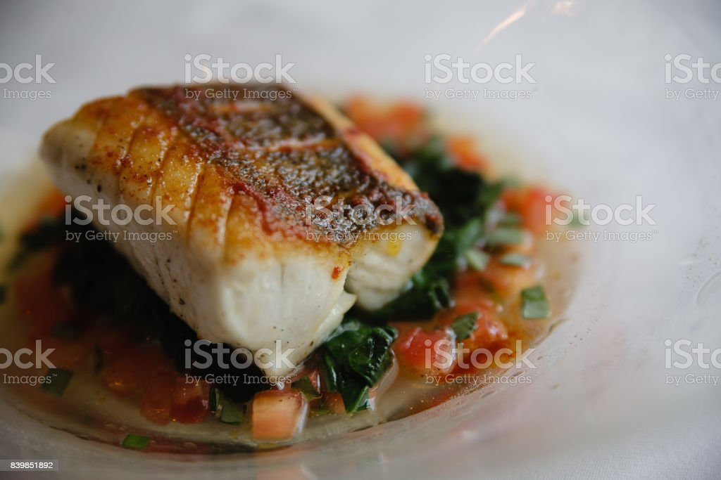 Seared sous vide cod filet on a bed of vegetables stock photo