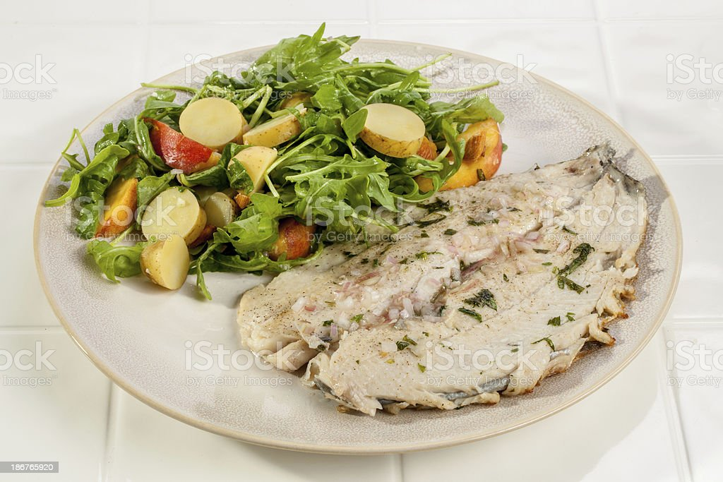 Seared Trout Dinner with Arugula Salad stock photo