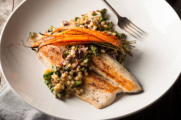 Seared Trout Pan Seared Trout with Carrots, Asparagus, Fregola and Radicchio. main course stock pictures, royalty-free photos & images