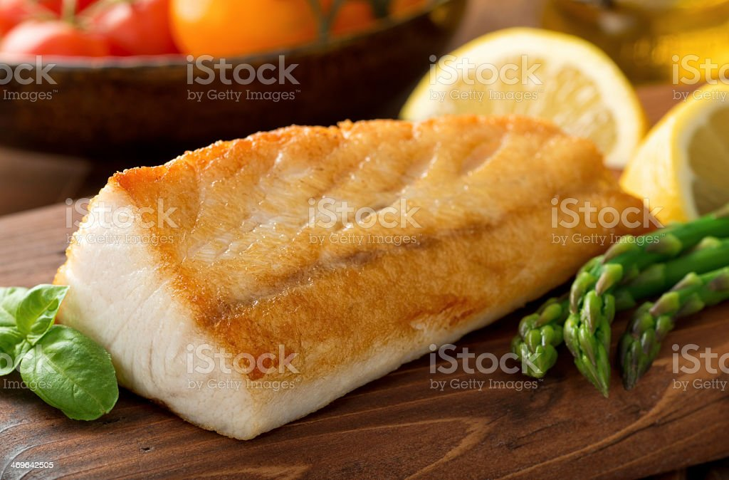Seared White Fish on a Wooden Board with Asparagus and Lemon stock photo