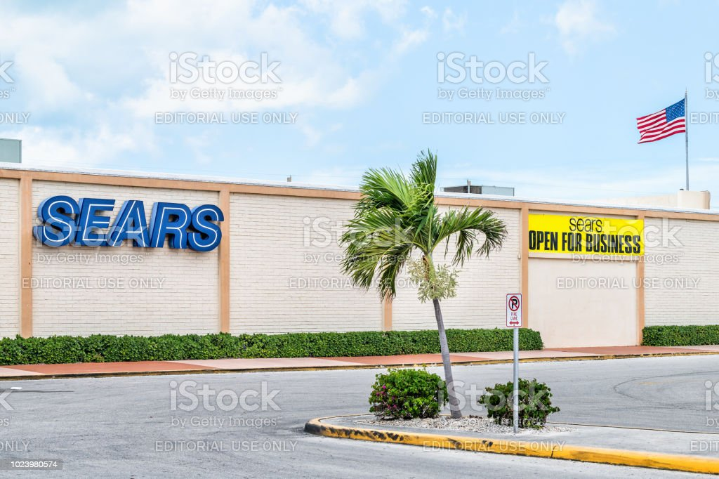 Sears department Store outlet with yellow sign Open for Business with nobody, American flag, road, street stock photo