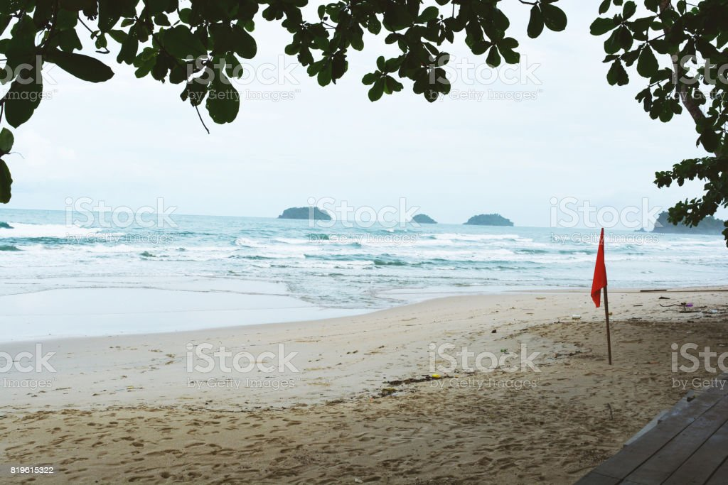 Seascape and red flag on beach with leaves.Beach and sea with wave in tropical. stock photo