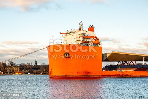 Seascape closeup side view of a large orange semi-submersible heavy-lift ship with large load entering harbor in Stockholm Sweden. The ship is carrying a large golden bridge all the way from China for the construction site Slussen in Sweden.