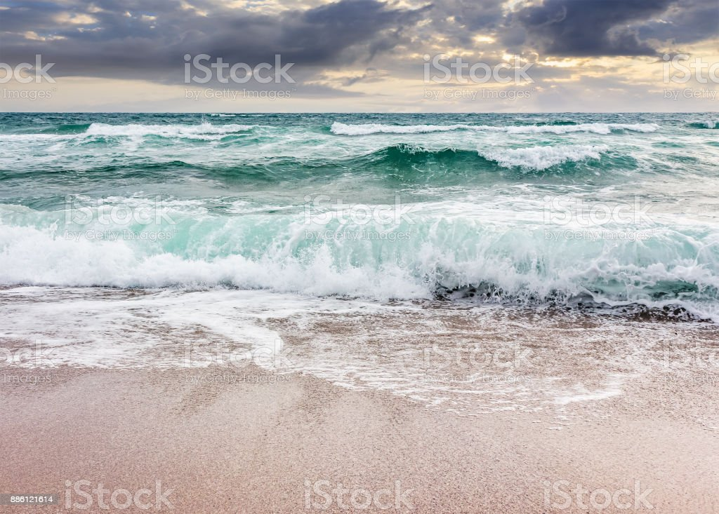 seascape in stormy weather at cloudy sunrise stock photo