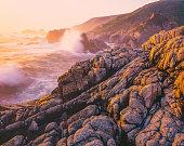 Seascape of Big Sur coastline with breaking wave in a rocky cove, Big Sur California