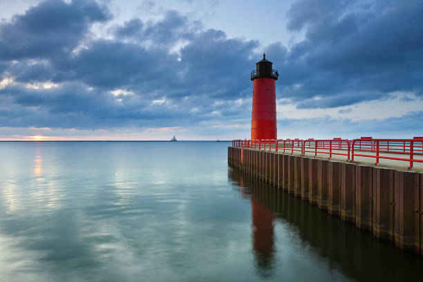 Seascape of Milwaukee Lighthouse with flat calm sea  Image of the Milwaukee Lighthouse at sunrise. milwaukee wisconsin stock pictures, royalty-free photos & images