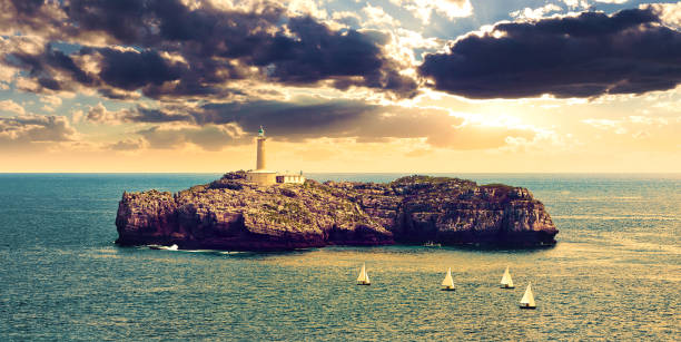 Seascape of sunset and wonderful sky. Boats sailing in the ocean Lighthouse on the sea over the rocks in Cantabria, Santander, Spain cantabria stock pictures, royalty-free photos & images