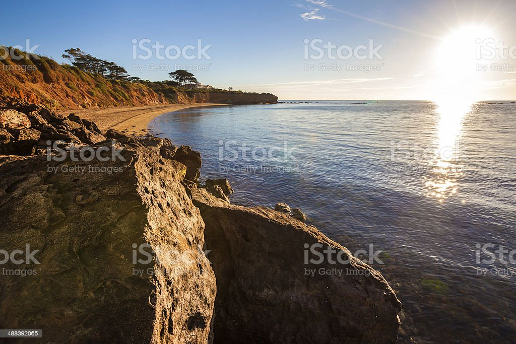 Seascape of Sunset overlooking house on a cliff stock photo