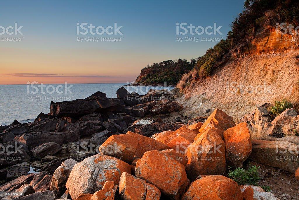 Seascape of Sunset with orange rocks on foreground stock photo