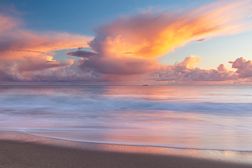 Seascape of warm pink storm cloud at sunset over the oceans shore, photographed with motion blur in California.