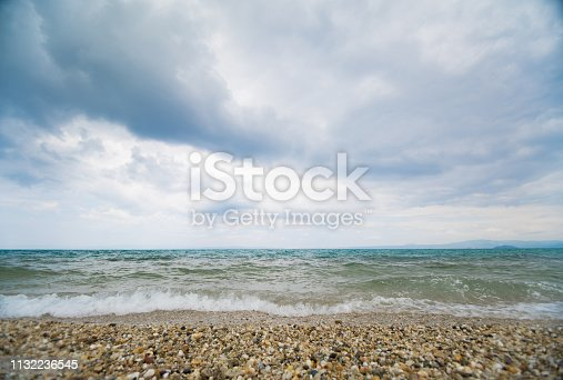 Seascape on an overcast day with high waves and clouds above the horizon.
