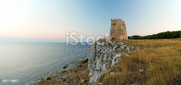 Seascape panorama with a tower on the edge of the cliff. Puglia, Italy.