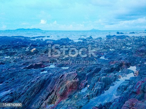 A seascape shot of rocks by the beach during a cloudy sunset. Shot was taken during blue hours and reveals beautiful colour and patterns on the rocks and the unique design of its form.