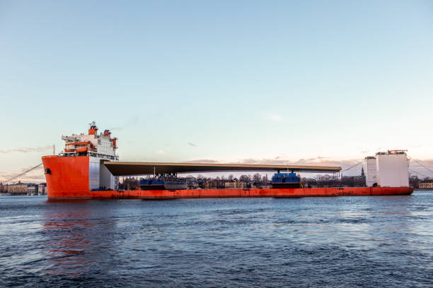 Seascape side view of a large orange semi-submersible heavy-lift ship with large load entering harbor in Stockholm Sweden. stock photo
