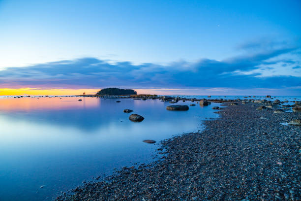 Seascape sunset with rocks and pebble coast of Baltic sea stock photo