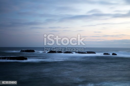 Pacific Ocean view in Punta Arenas, California at sunset. clear sky over the ocean where a rock formation could be seen with waves clashing against it before reaching shore. this is one of many travel destinations along the California coast.