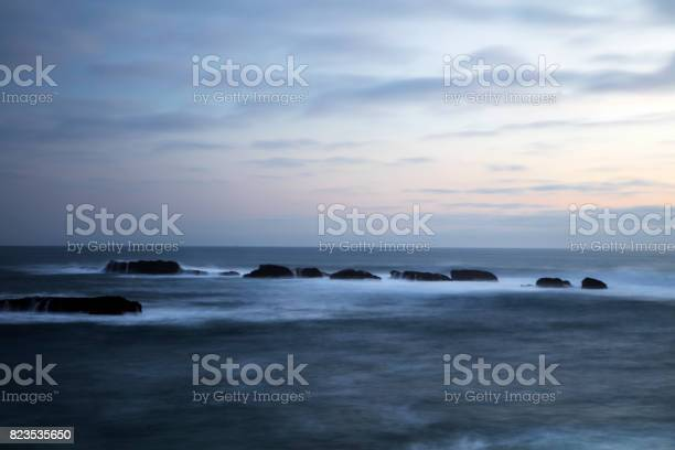 Photo of seascape view at sunset with rocks formation out in the Pacific ocean.