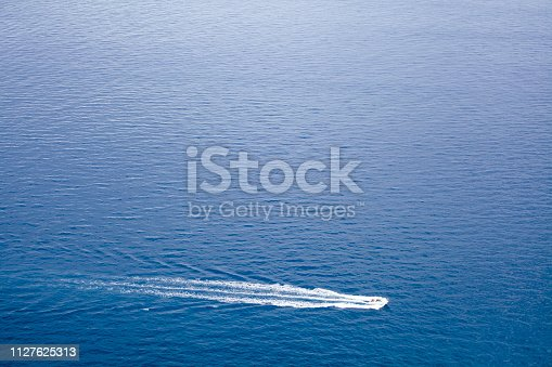 Seascape, blue water surface and nautical vessel. Full frame image suitable for background purposes. Copy space available on the upper side of the image. Madeira island, Portugal.